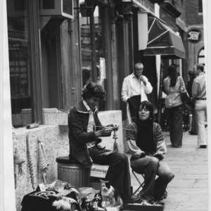 Two young people selling corn dollies on the street in Islington, London