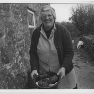 Eileen Thomas holding a bucket of roots. Middle Georgia Farm, Nancledra, Penzance, Cornwall.